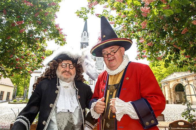 """Hofnarr Joseph Fröhlich und """"Zeremonienmeister"""" Karl von Dräsn im barocken Kostüm vor der schönen Kulisse von Schloss Burgk, wo am 19. Mai 2019 das Saturnus-Fest stattfindet."""