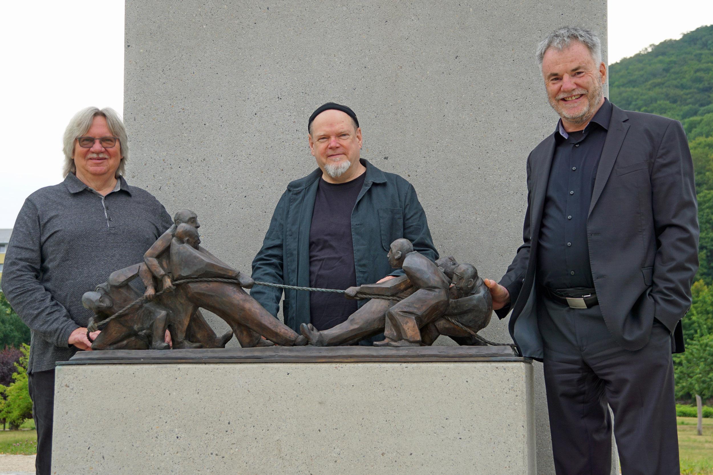 """Oberbürgermeister Uwe Rumberg, Künstler Olaf Stoy und der Zweite Bürgermeister Jörg-Peter Schautz (v.r.n.l.) vor der Figurengruppe """"Tauziehen"""" auf dem Freitaler Neumarkt."""